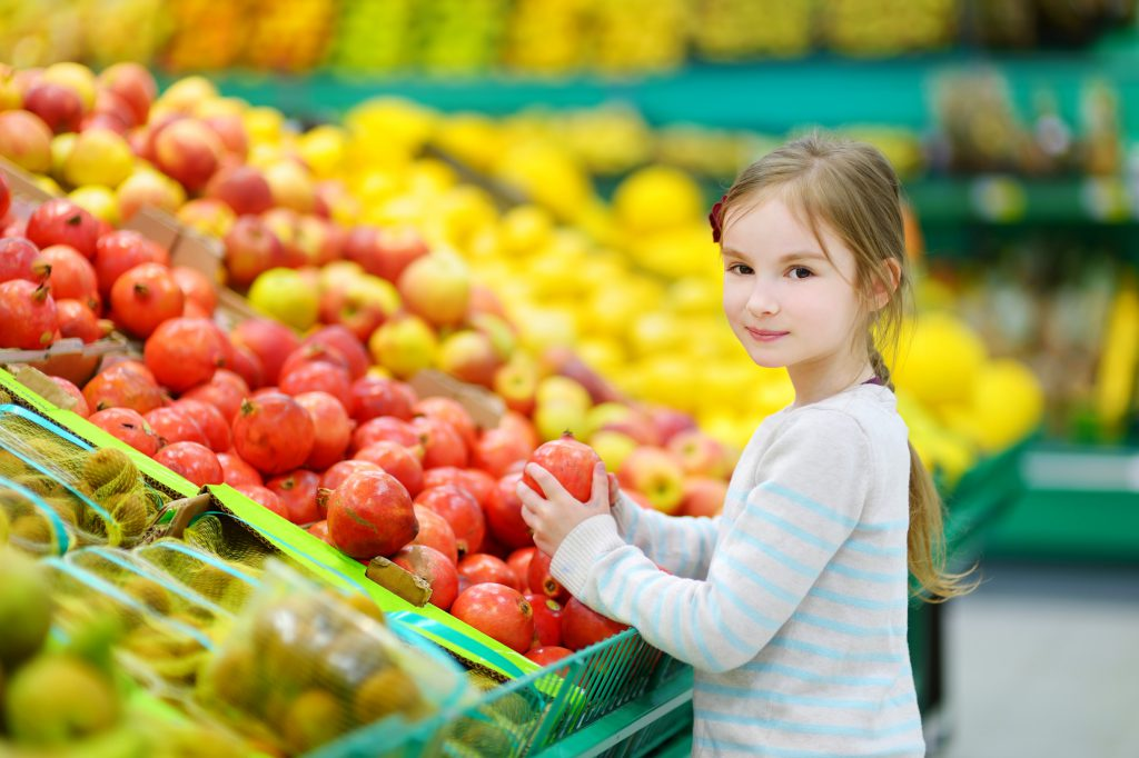 Young girl in fruit section of supermarket